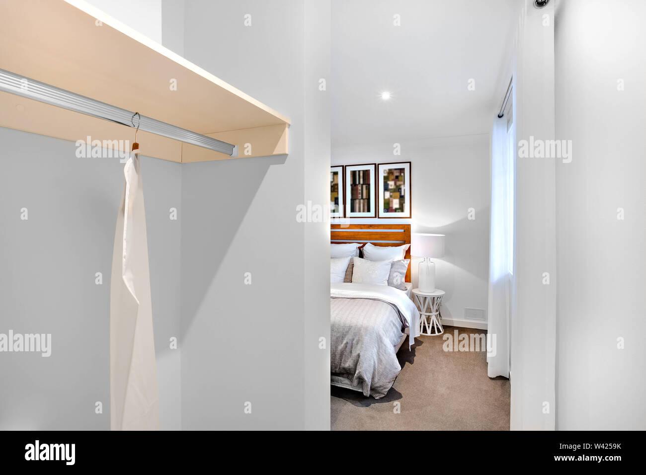 Camera da letto ingresso con pareti bianche e abiti appendiabiti accanto alla camera da letto finestra con una lampada e biancheria da letto Immagini Stock