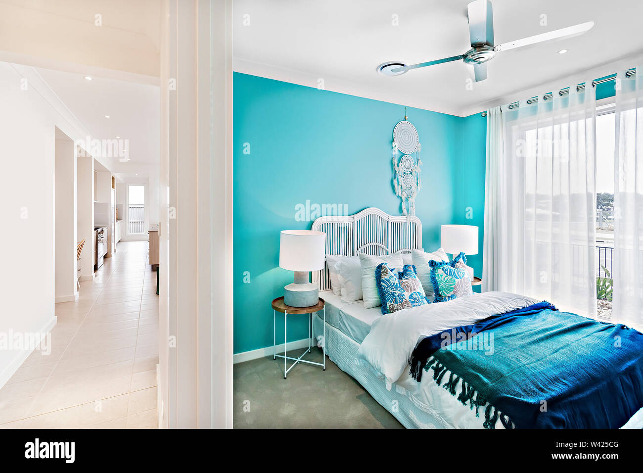 Camera con letto matrimoniale e coloratissimi cuscini, letti confortevoli tra cui disegni, le pareti sono di color bianco, cuscino piccolo è bello, all'interno di camere di un APA Immagini Stock