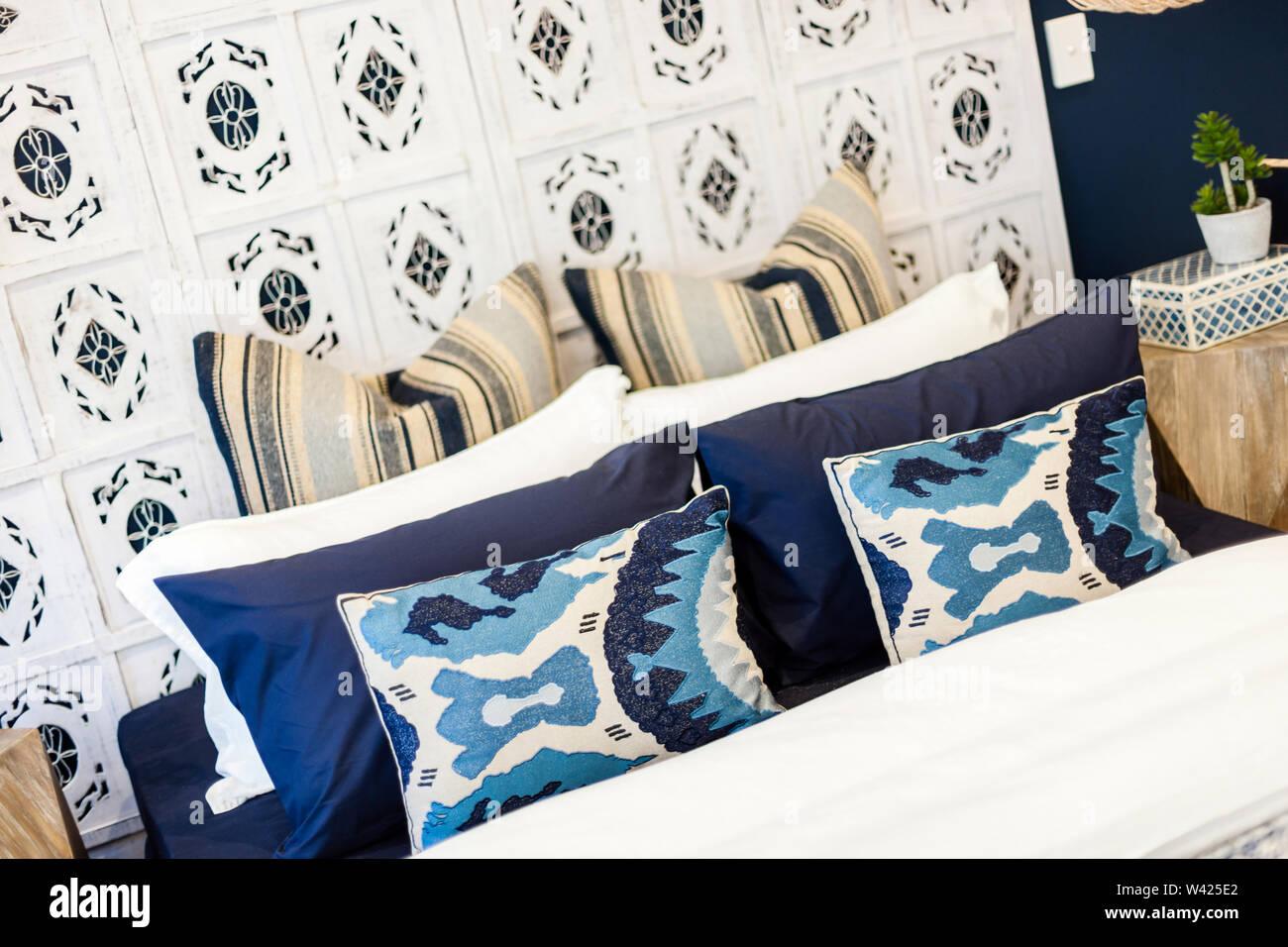 Un letto con cuscini e cuscini in sfumature di blu contro un bianco di supporto del letto e un letto bianco foglio, con un elegante tavolo laterale con un piano di piccole dimensioni Immagini Stock