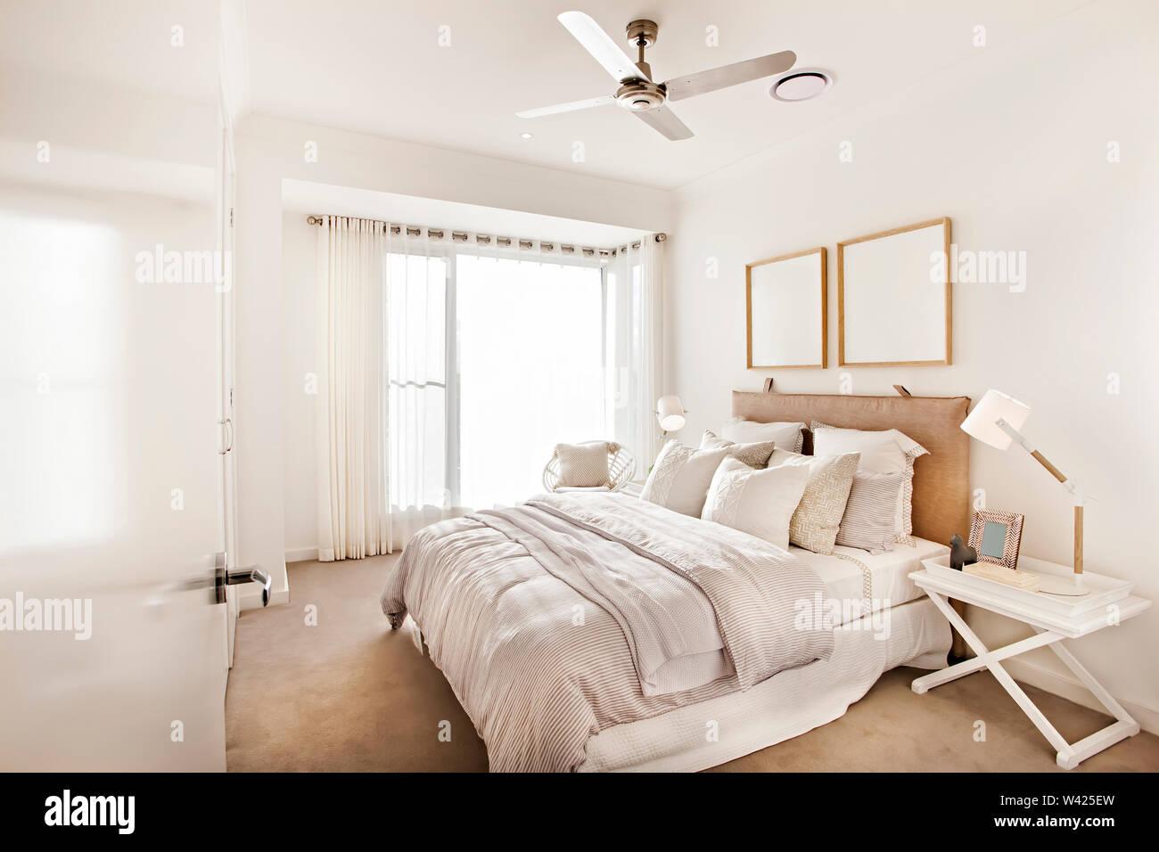 Camera Classic con letto moderno design, letti confortevoli con disegni, le pareti sono di colore bianco e i cuscini sono belli, all'interno della camera di un appartamento. Immagini Stock