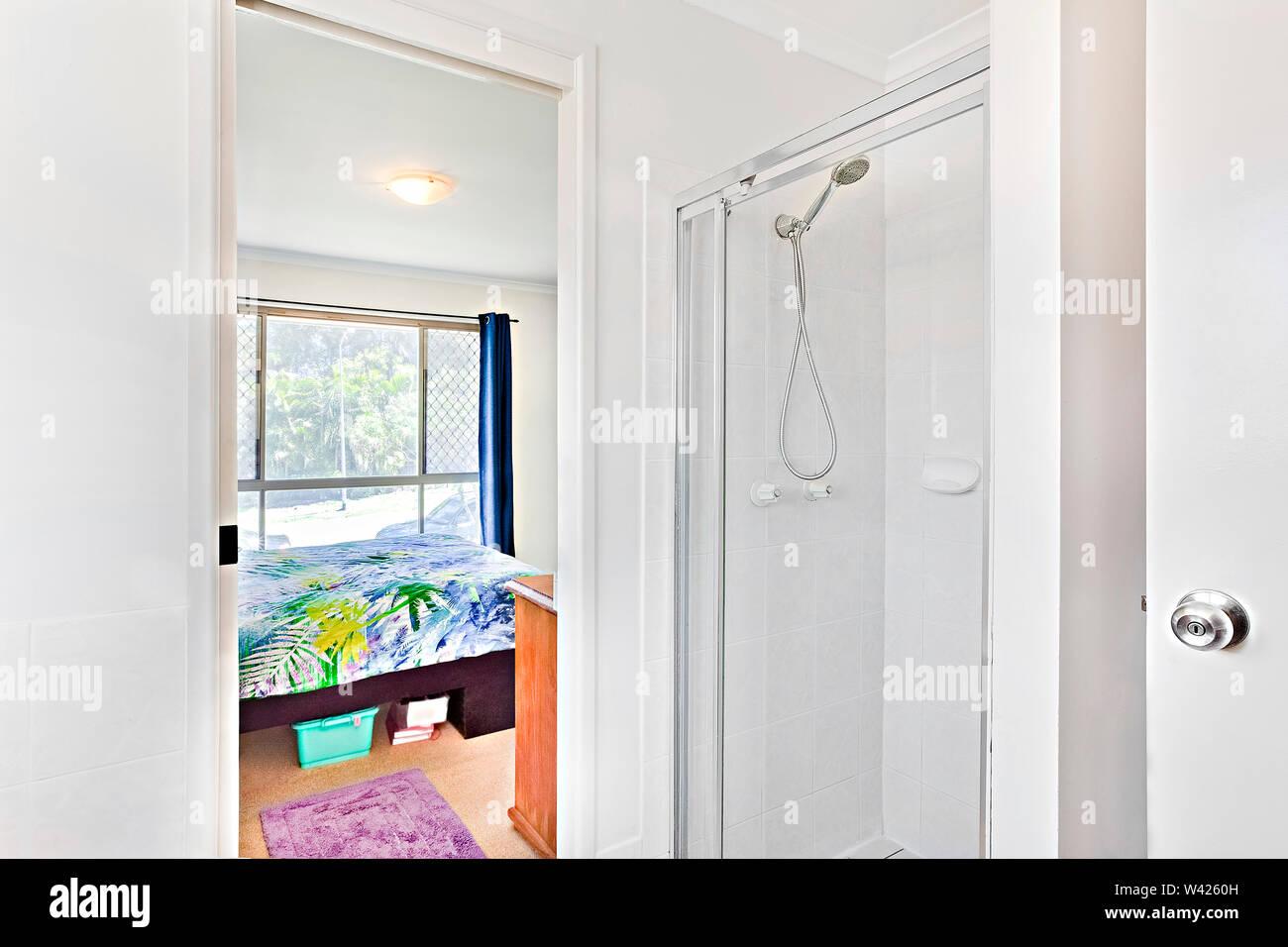 Area lavaggio all'interno di un appartamento, letto confortevole con disegni, le pareti sono di colore bianco e i cuscini sono belli, all'interno di un ambiente di appartamenti. Immagini Stock