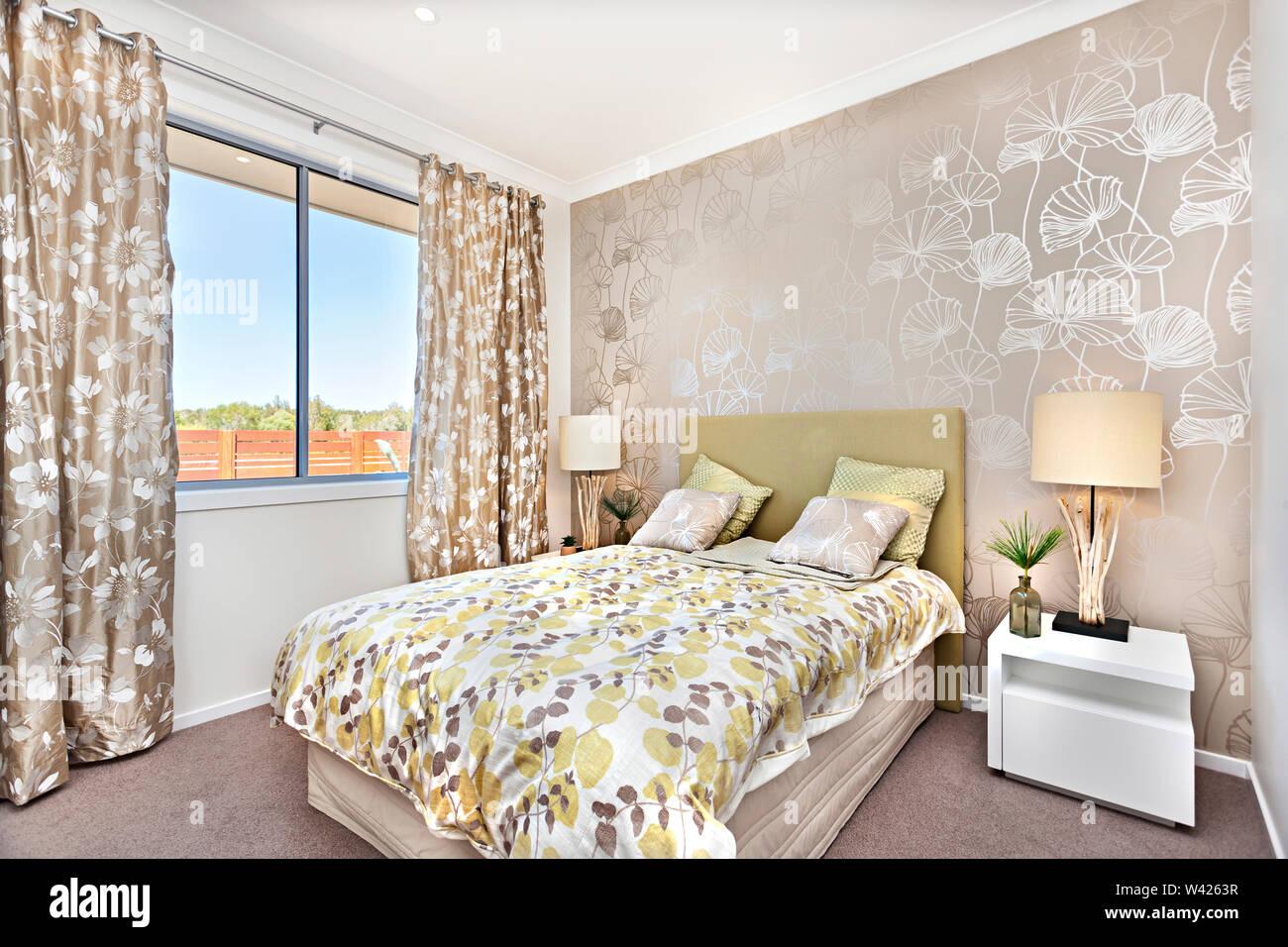Letto di lusso è po' di altezza dal pavimento moquette e ha una luce di colore lenzuolo con foglie di vite e modelli, quattro colore grigio cuscini e giallo Immagini Stock