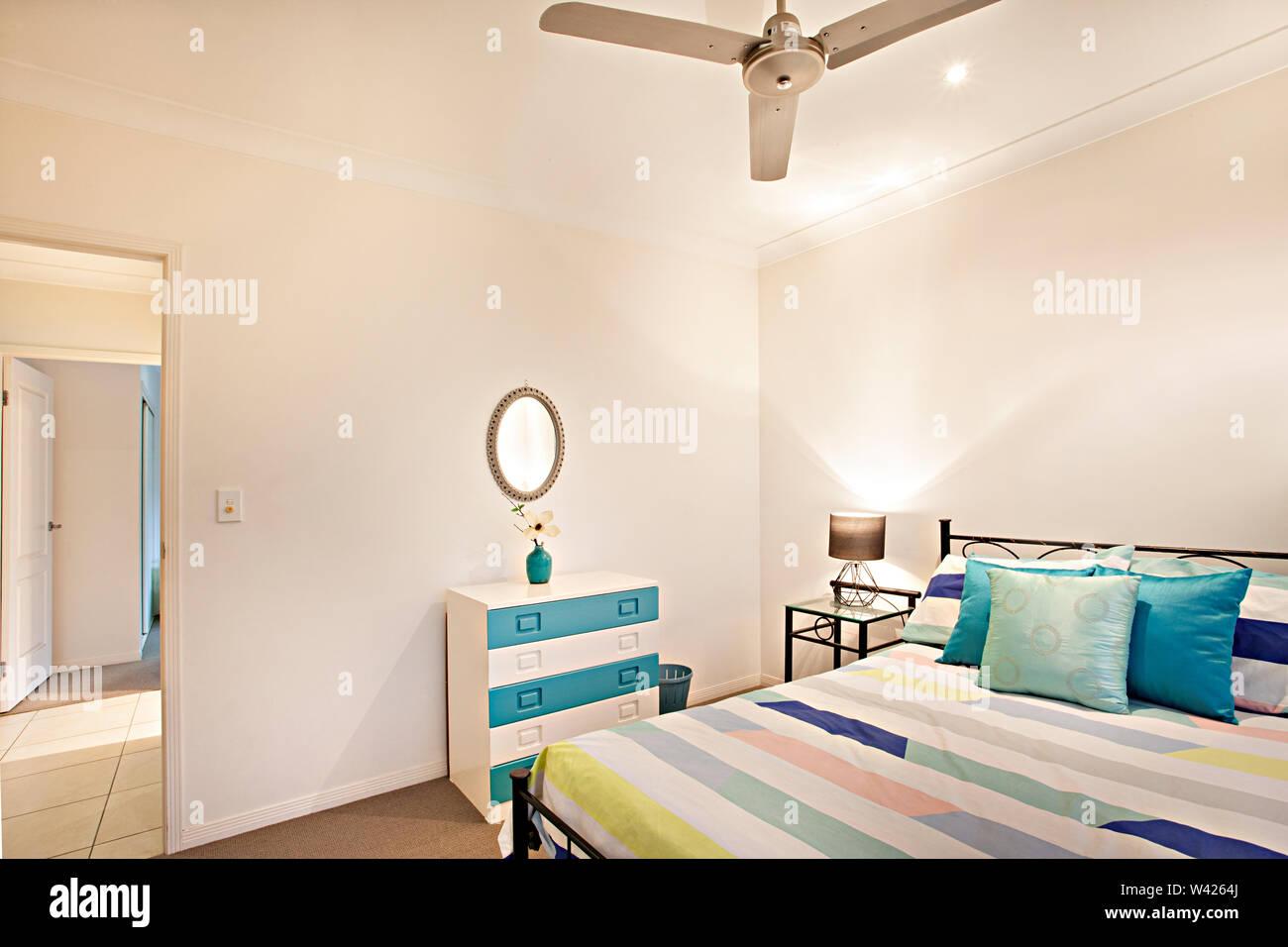 Foglio di letto con disegni sul letto e vaso vicino a specchio, letto confortevole con disegni, le pareti sono di colore bianco e i cuscini sono belli, all'interno di una sala a parte Immagini Stock