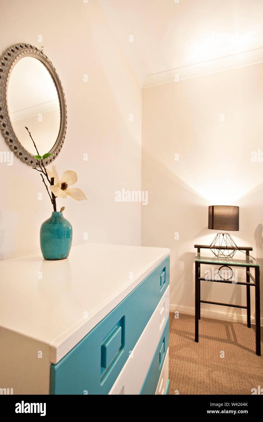 Vaso di fiori vicino alla parete a specchio con lampada, letto confortevole con disegni, le pareti sono di colore bianco e i cuscini sono belli, all'interno della camera di un appartamento. Immagini Stock
