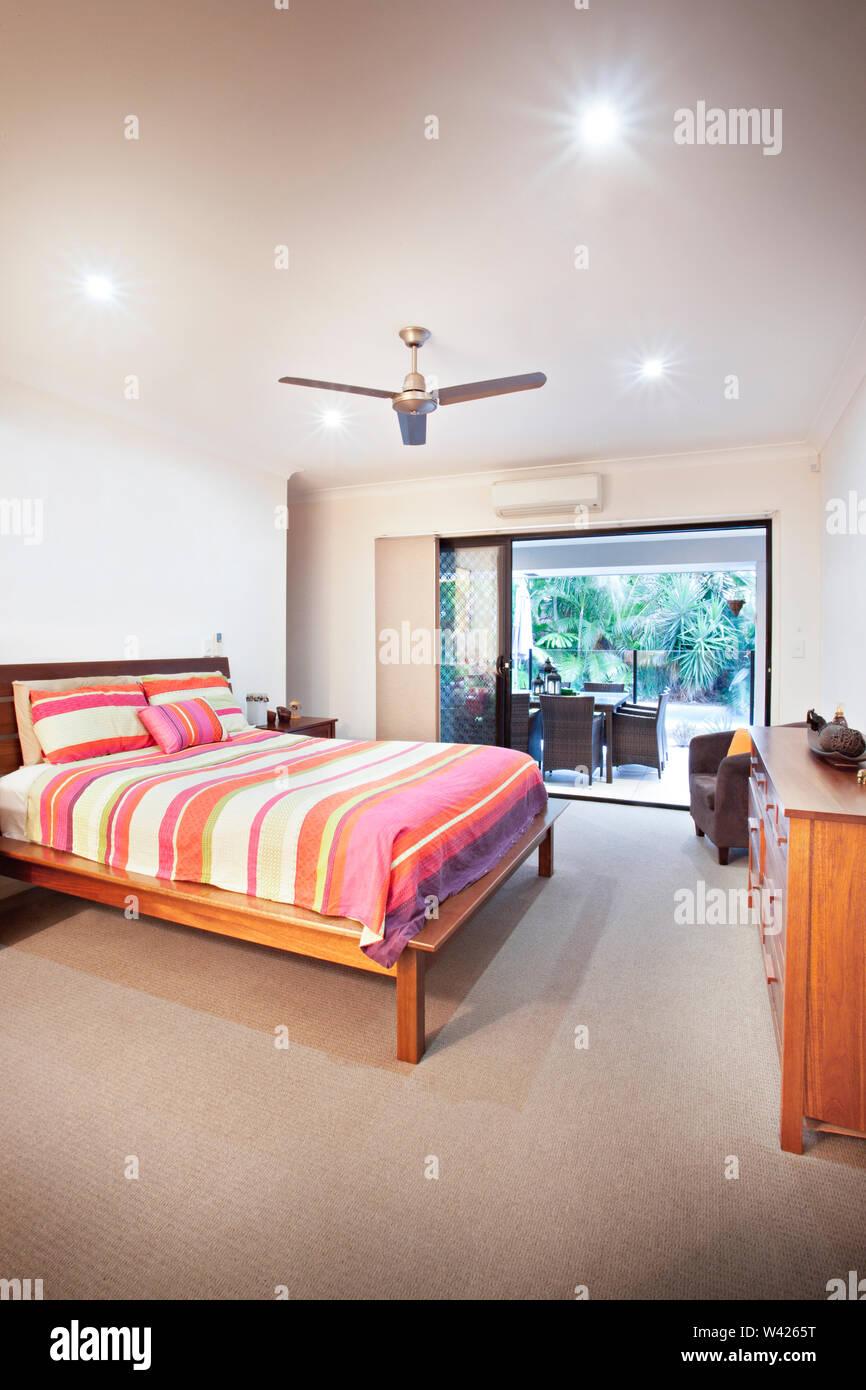 Vista laterale del letto matrimoniale con tavolo, letti confortevoli con disegni, le pareti sono di colore bianco e i cuscini sono belli, all'interno della camera di un appartamento. Immagini Stock