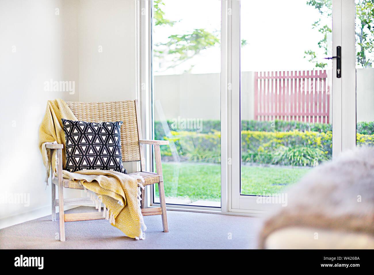 Cuscino con una sedia di legno e un foglio giallo accanto a una porta per il giardino esterno vista, inclusa una illuminazione a luce del sole e il verde prato vicino a Immagini Stock