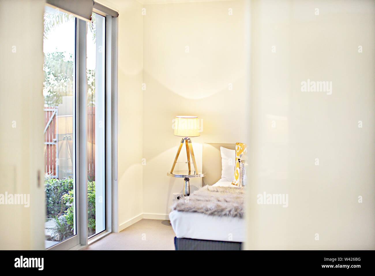 Guardando alla moderna camera da letto ingresso con una luce gialla lampeggiante accanto a cuscini sul letto con coperta di pelliccia, vi sono luci sulla parete accanto a th Immagini Stock