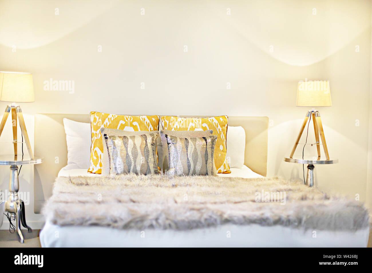 Letto con lampade lampeggianti compresi cuscini e coperta di lana, ci sono due lampade da tavolo con realizzato in legno intorno sulla superficie di argento, Immagini Stock