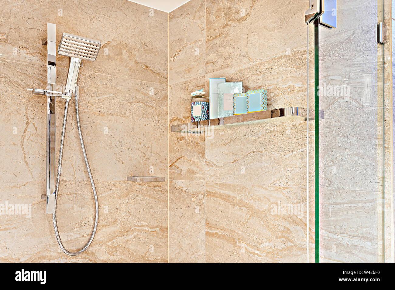 Un contemporaneo stile di doccia a mano con un montato a parete in vetro e ripiano in metallo Immagini Stock