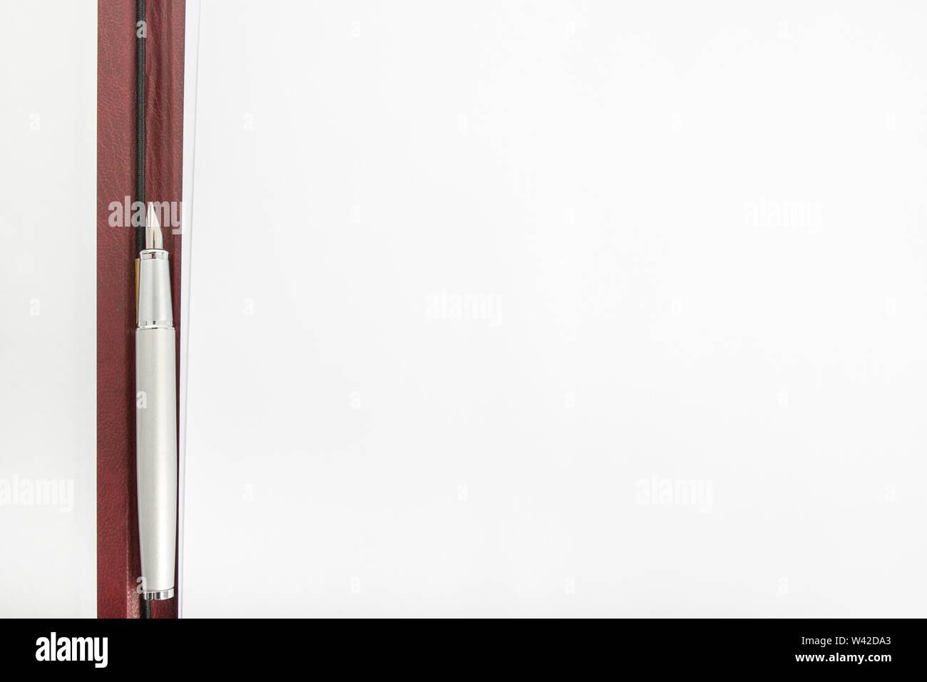 Vista dall'alto di una penna che giace tra due fogli di carta in una aperta la cartella in pelle. Immagini Stock
