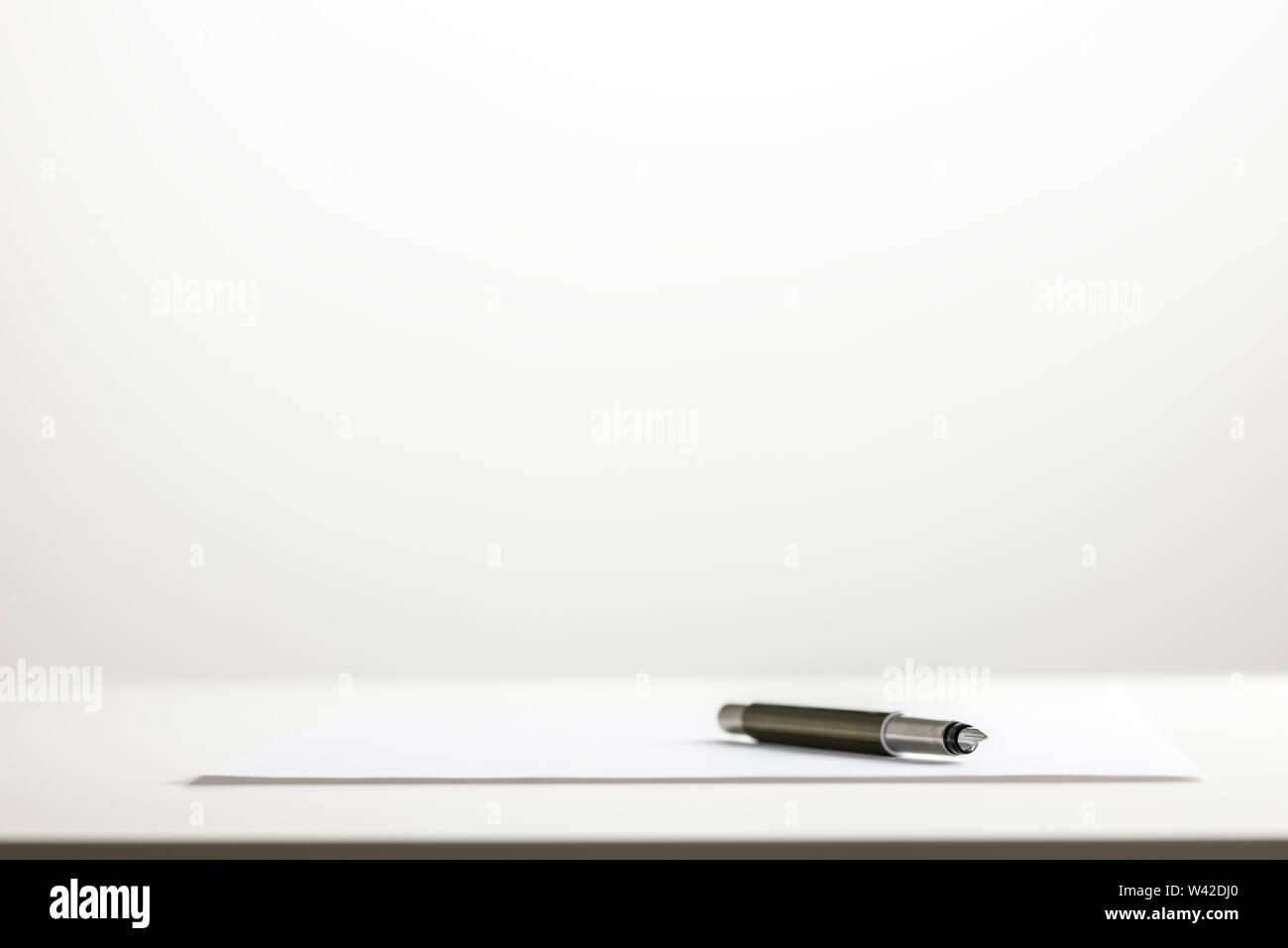 Basso angolo vista di una penna su un foglio di carta bianca carta su un desktop di bianco con un bianco muro bianco in background con abbondanza di copyspace. Immagini Stock