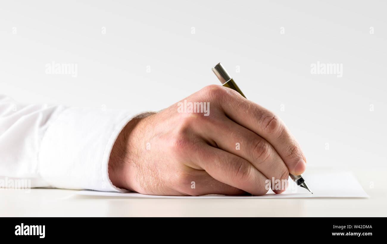 Close up della mano di un uomo che scrive su un foglio di carta con una penna stilografica concettuale del manoscritto o in corrispondenza della firma di un accordo o b Immagini Stock