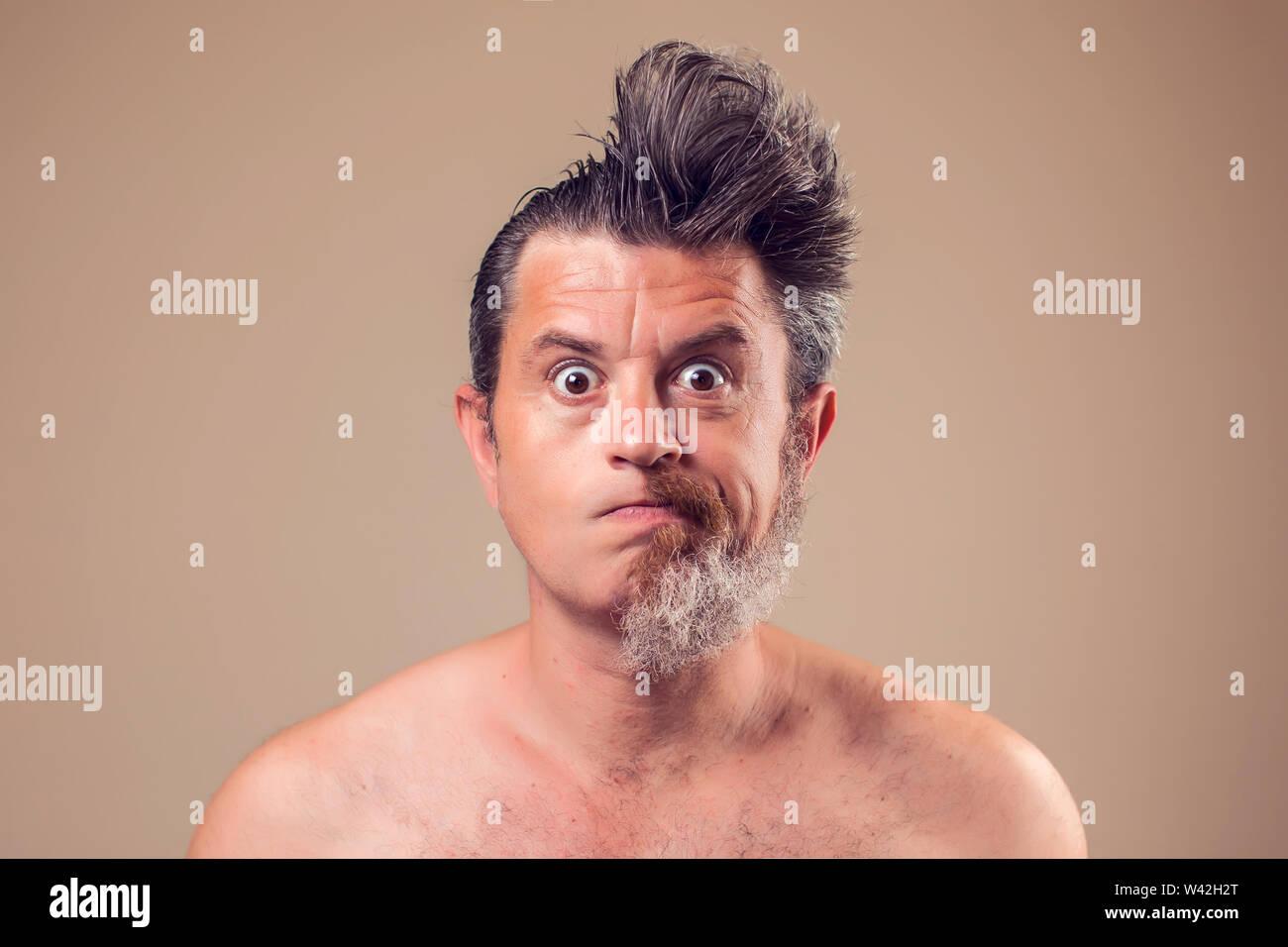 Un ritratto di uomo con la metà di barba e capelli su sfondo marrone Foto Stock