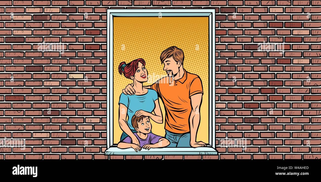 Una famiglia giovane con un ragazzo figlio nella finestra della casa Immagini Stock