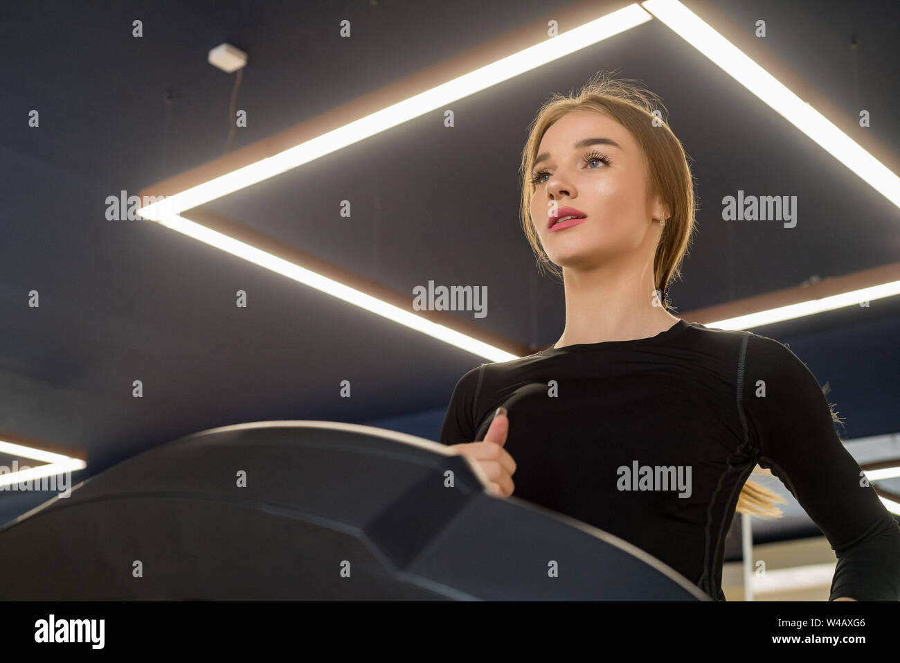 Ritratto di giovane donna di montare sul moderno tapis roulant in palestra Foto Stock