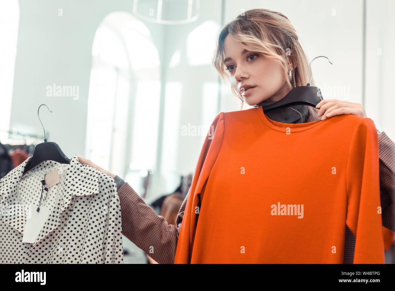 Biondo e sentimento donna premurosa mentre la scelta di vestire Foto Stock
