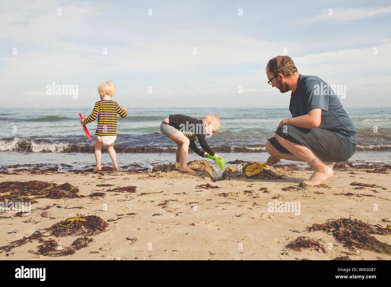 Padre di due bambini che giocavano sulla spiaggia Foto Stock