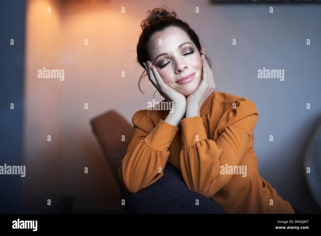 Ritratto di donna sorridente con gli occhi chiusi seduti sul divano di casa Foto Stock