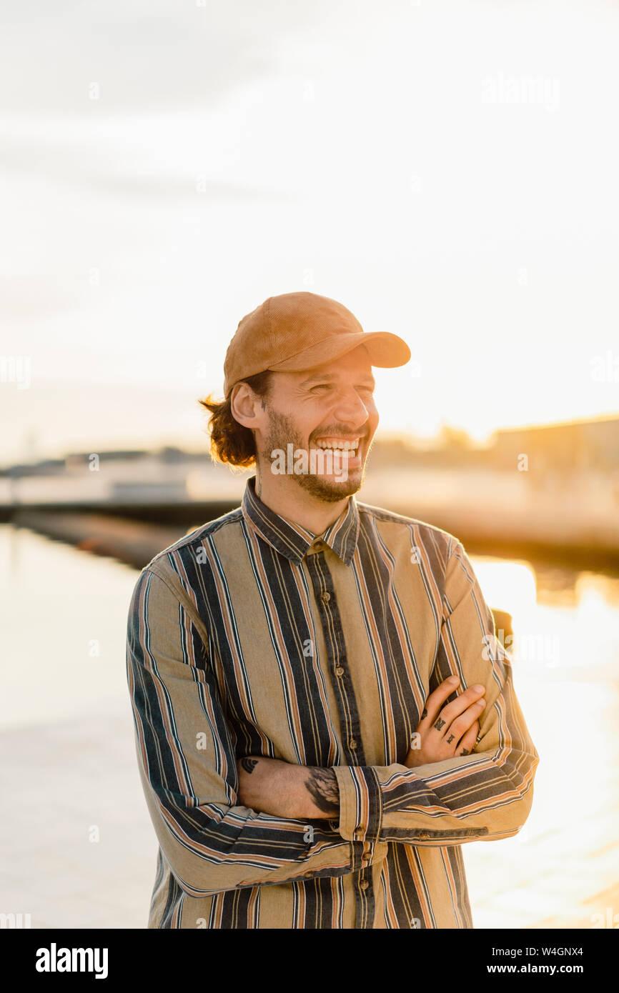 Prtrait di ridere uomo che indossa cappello da baseball e strisce shirt al tramonto Foto Stock