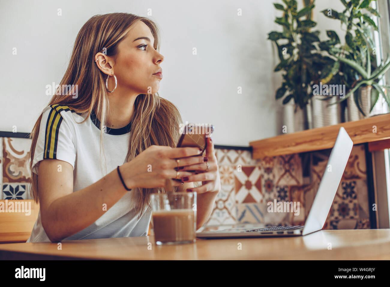Giovane donna utilizzando il telefono cellulare e il computer portatile in cafe Foto Stock