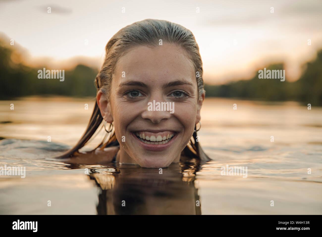 Giovane donna nuoto nel lago al tramonto Foto Stock