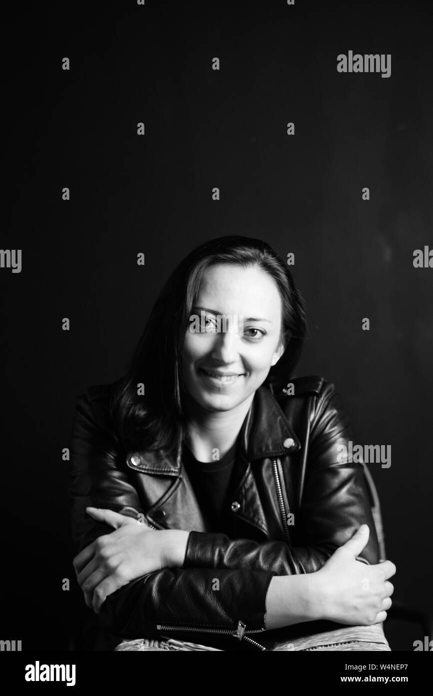 Ritratto in studio di un attraente giovane donna in un nero giacca di pelle contro uno sfondo semplice Foto Stock