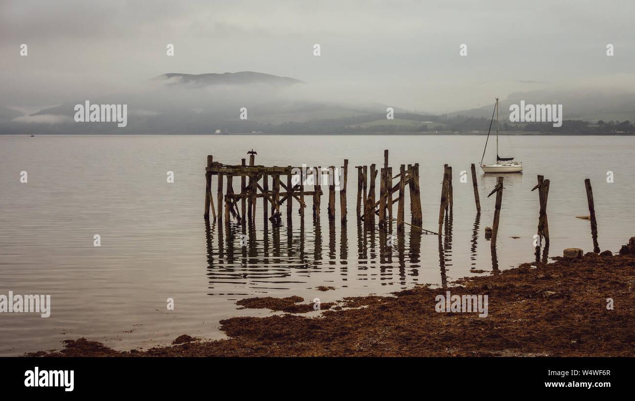 Il vecchio, rovinato molo in legno con le montagne alle spalle in una nebbiosa giorno - Porto Bannatyne, Isle of Bute, Scozia Foto Stock