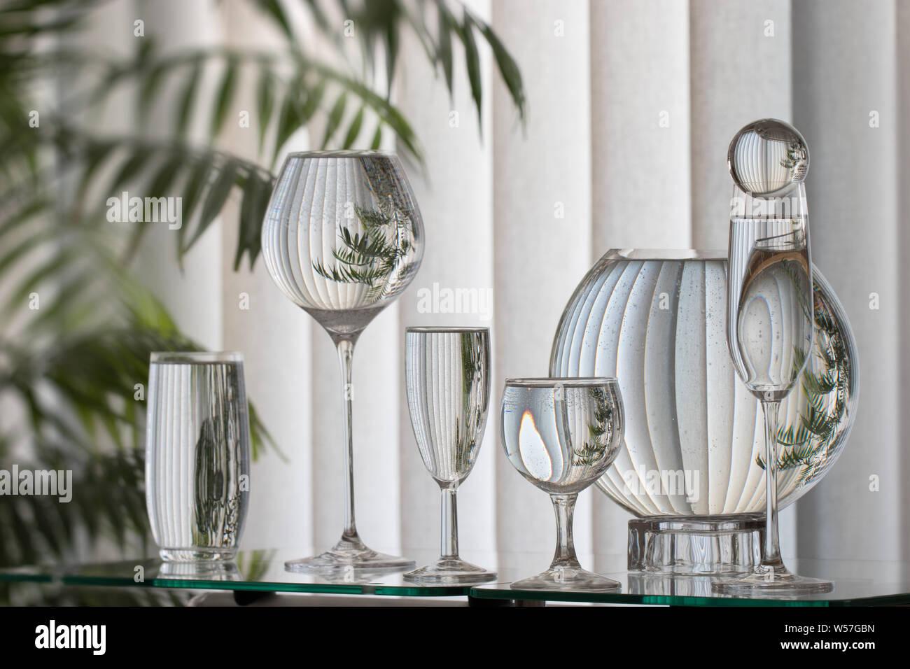 Diverse mit Wasser gefüllte Gläser stehen auf einer Glasfläche. Dahinter eine graue Senkrecht-Jalousie mit einer grünen Palme un linker Seite. Jede ge Foto Stock