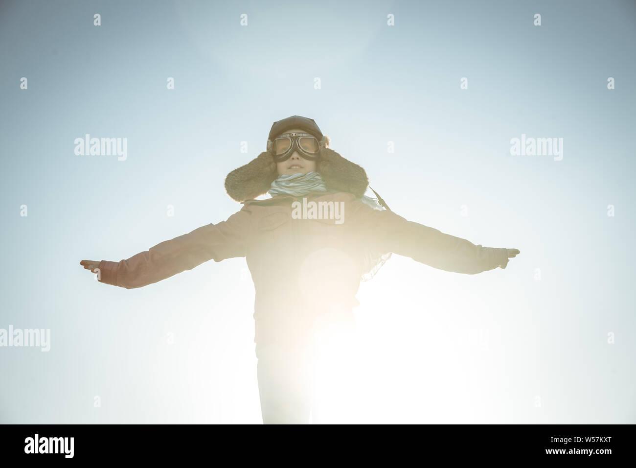 Bel ragazzo gioca felicemente gara con aereo gioiosamente fingendo di decollare dissimulata come un vintage pilota di aviazione hat, occhiali maschera giacca in pelle un Foto Stock