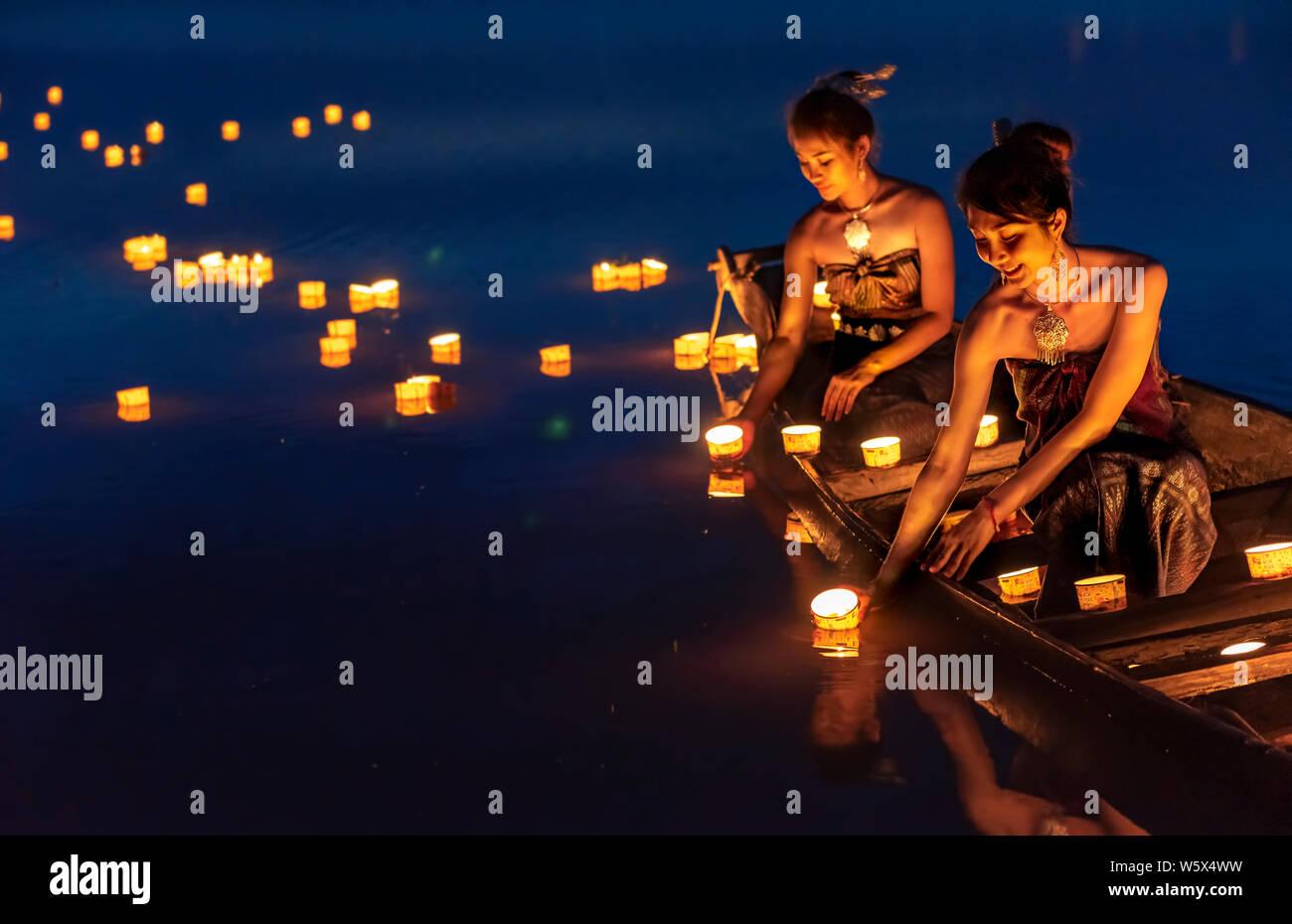 Giovani ragazze asiatiche lanterne galleggianti nel lago. Il festival può provenire da un antico rituale pregando rispetto all'acqua alcolici. Foto Stock