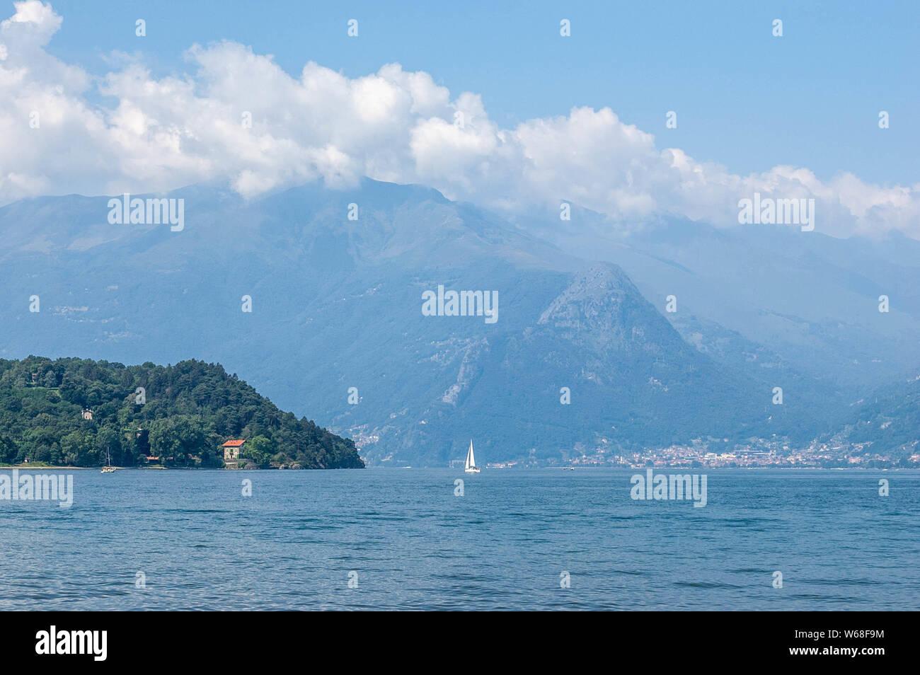 Vista del lago di montagna e il pomontory su una soleggiata giornata estiva. Distretto del Lago di Como, Colico, Italia, Europa. Foto Stock