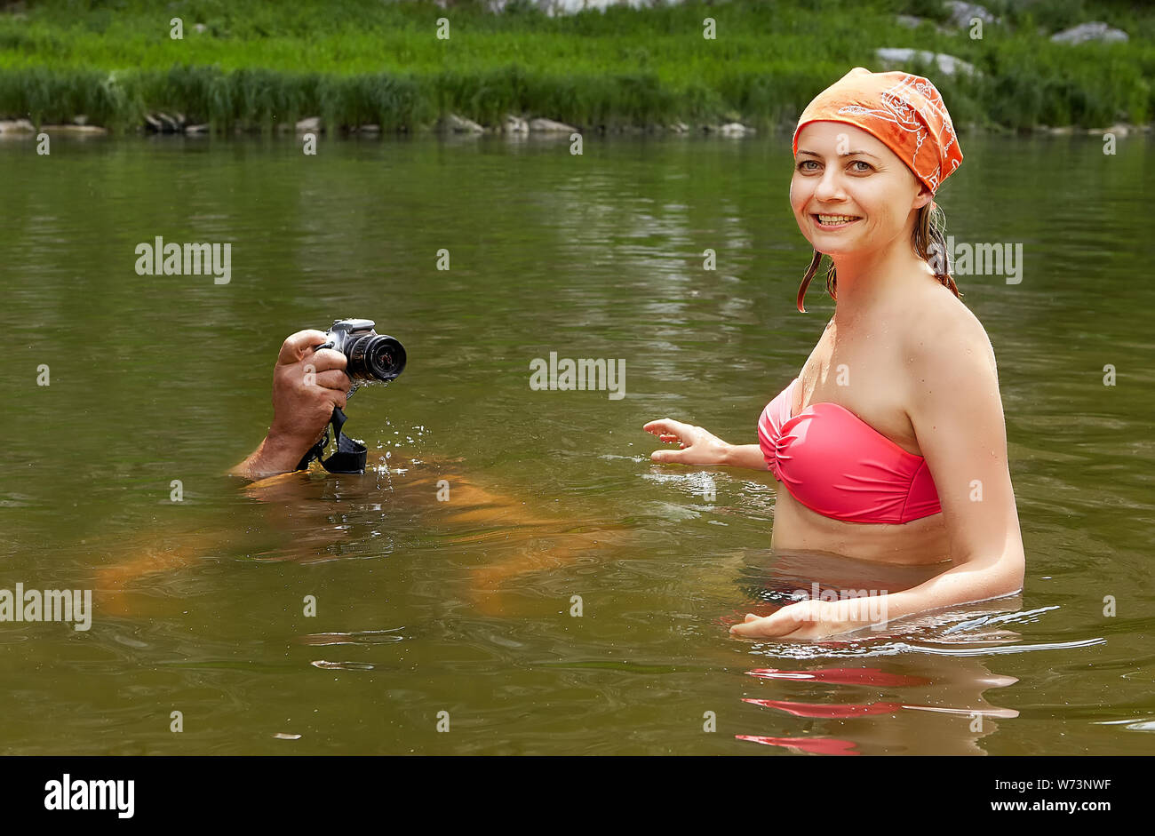 Giovane bella donna bagnato in costume da bagno è in piedi nel fiume mentre l uomo è scattare foto con la fotocamera digitale dalla superficie dell'acqua, eco-turismo. Foto Stock