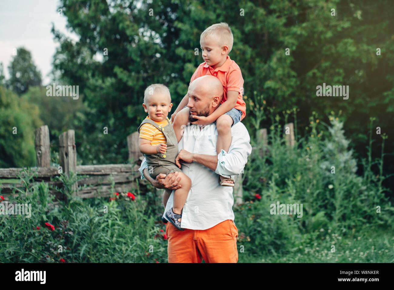 Padre caucasica abbracciando la riproduzione con figli i ragazzi nel parco sulla giornata d'estate. Papà tenendo il trasporto di bambini i bambini. Un autentico stile di vita toccante momento di gara. Foto Stock