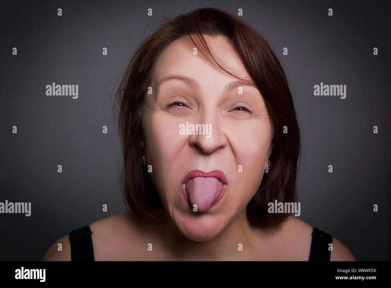 Donna smorfie nella parte anteriore della fotocamera su sfondo nero Foto Stock