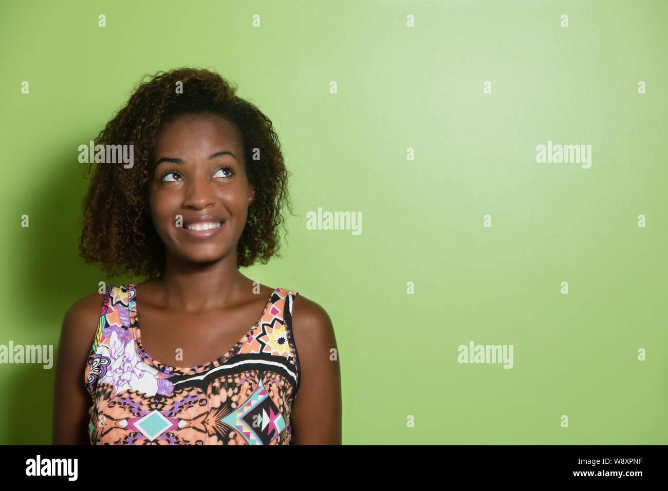 Bella americano africano donna che guarda lateralmente ad una parete verde Foto Stock