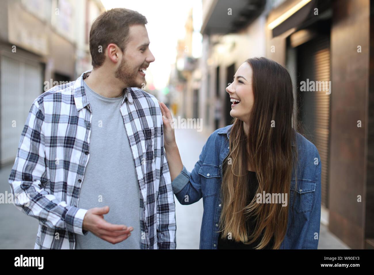 Vista anteriore verticale di un felice amici flirtare camminando verso di voi per la strada Foto Stock