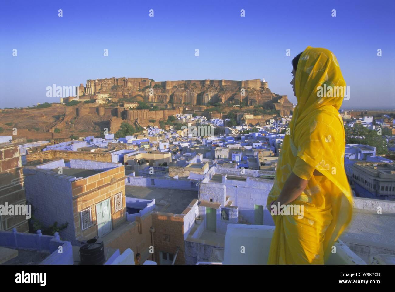 Una donna in un sari giallo guardando verso il 'città blu' e fort, Jodhpur, stato del Rajasthan, India, Asia Foto Stock