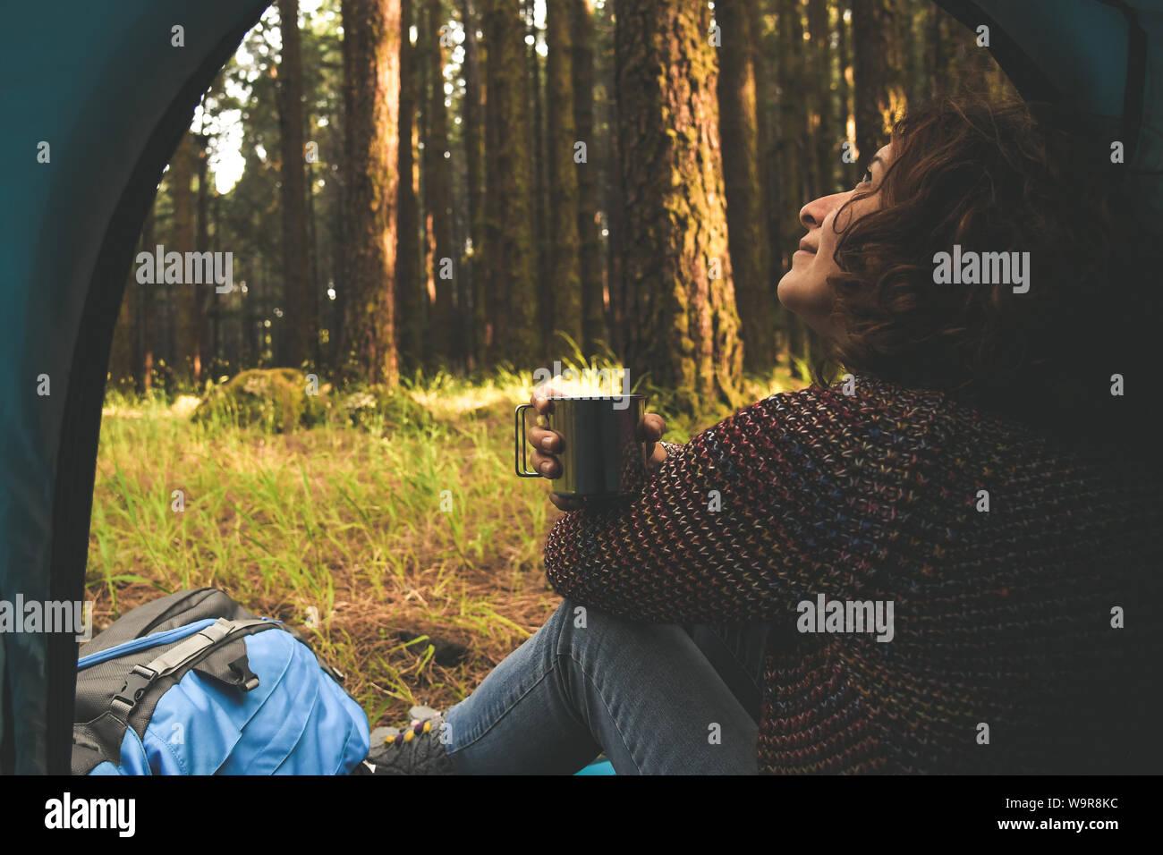 Bella donna seduta nella tenda in cerca della natura selvaggia fuori beve una tazza di caffè alla moda ragazza sola rilassante nella foresta dopo un trekking h Foto Stock