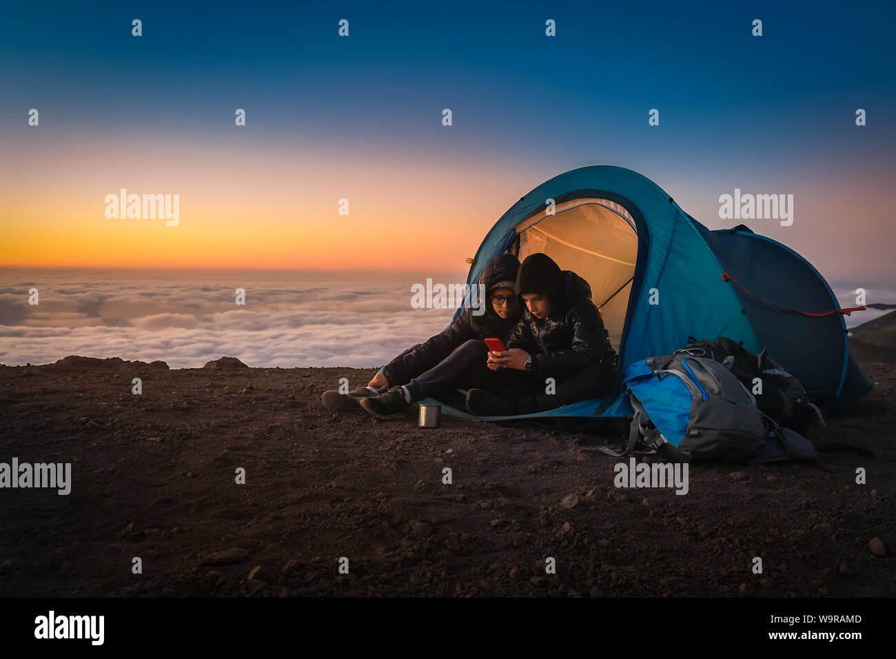 Due ragazzi tenendo selfie seduti in una tenda da campeggio