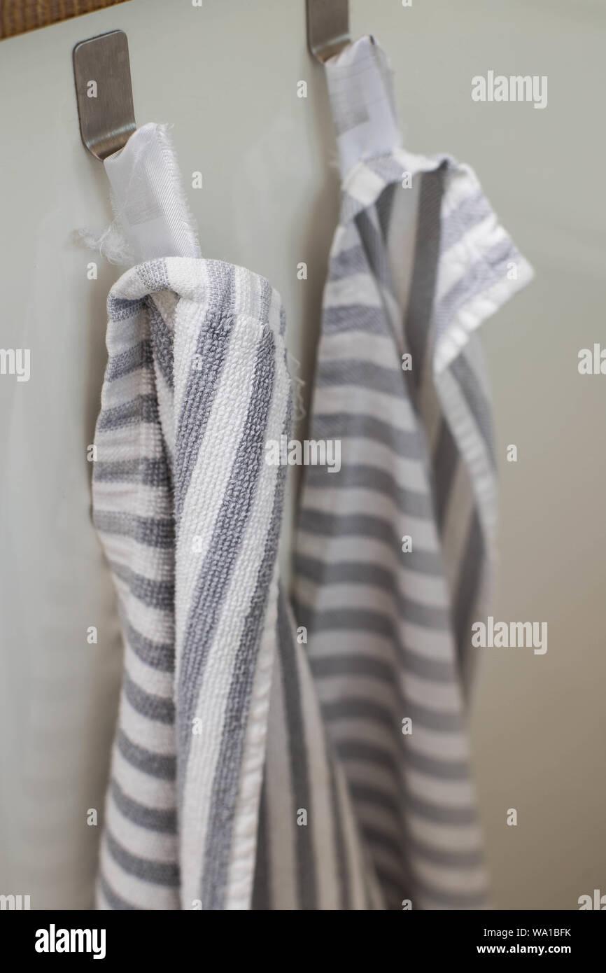 Due asciugamani da cucina appeso a ganci in una cucina di close-up Foto Stock