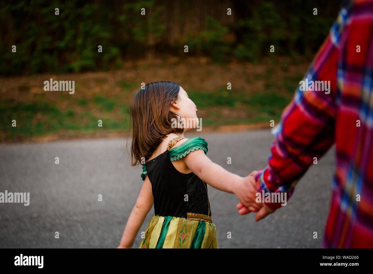Un piccolo bambino in un costume principessa trattiene il suo padre le mani su una passeggiata Foto Stock