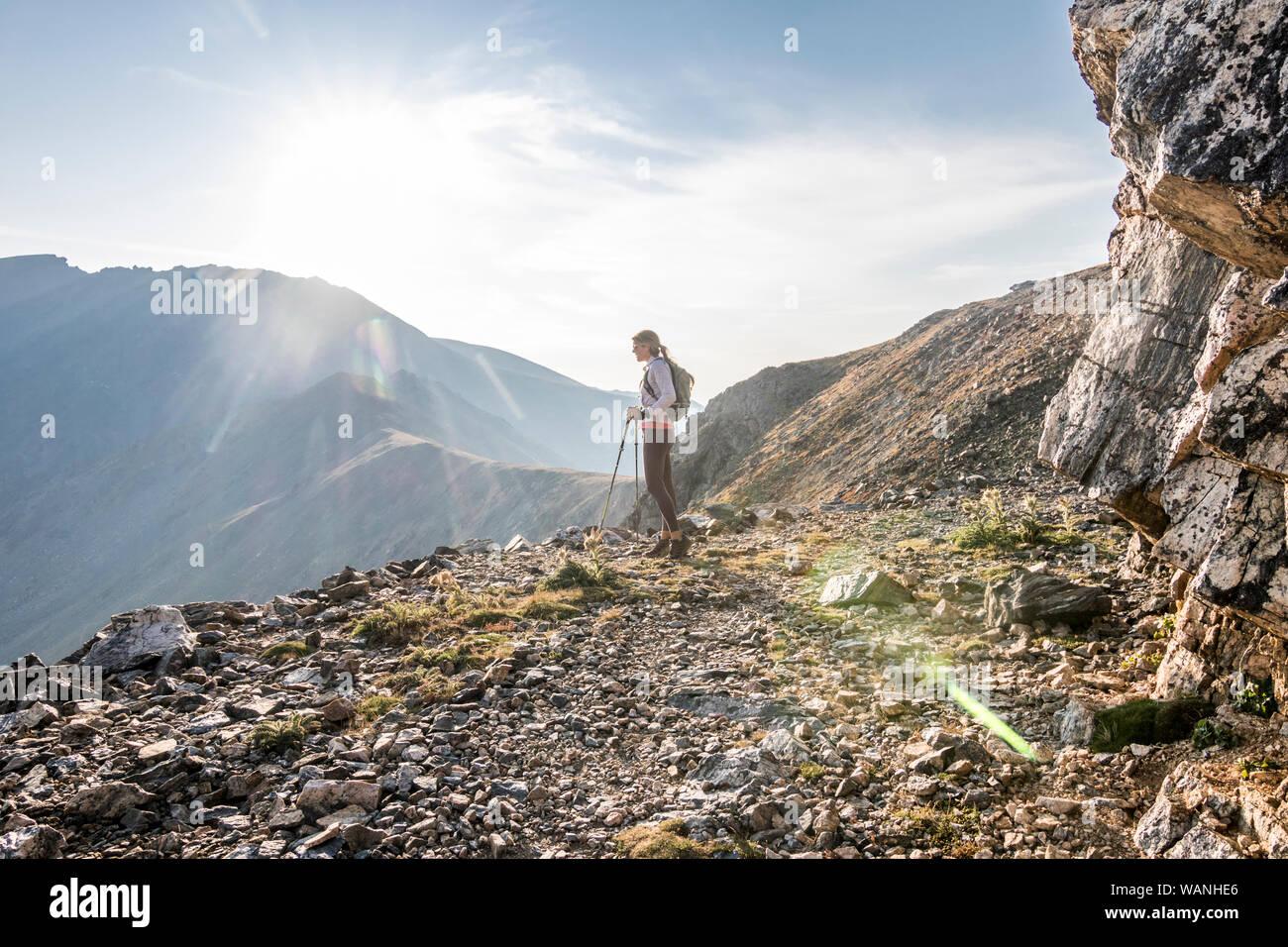 Una giovane donna trail runner si prende una pausa in alto sul Arapaho Pass Foto Stock