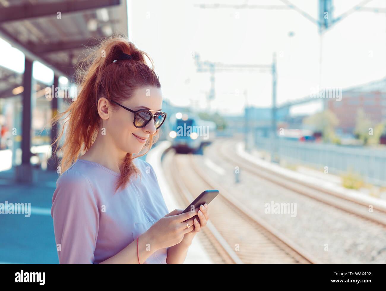 Giovane donna con il suo telefono cellulare sulla piattaforma della metropolitana, controllo messaggi sms e-mail o orari dei treni. Ragazza texting sullo smartphone mentre il treno cittadino approa Foto Stock