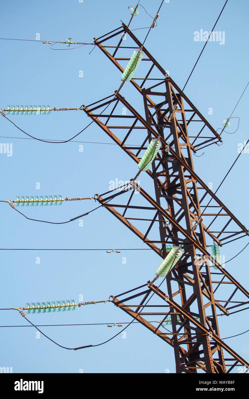 Vista dal basso su linee elettriche ad alta tensione contro blu cielo privo di nuvole Foto Stock