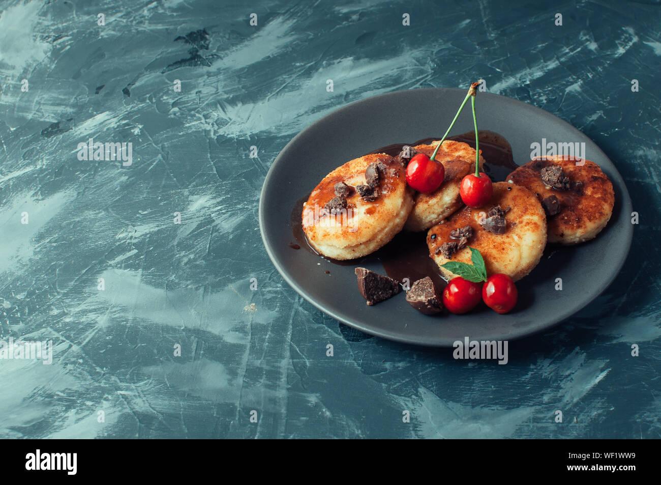 Il cibo della colazione gustosa concetto. La cheesecake, cheesecake, formaggio frittelle con ciliegie e cioccolato su uno sfondo nero tabella di calcestruzzo. Clos Foto Stock