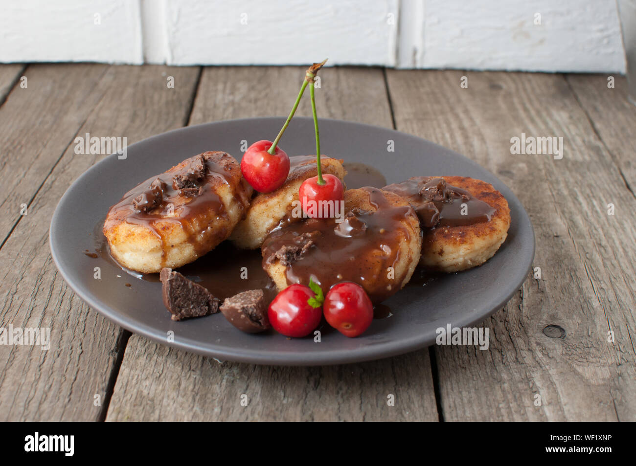 Colazione Gourmet - frittelle di cagliata, cheesecake, cagliata frittelle con ciliegie e cioccolato in una piastra di marrone. Salubre dessert su una tavola di legno in un r Foto Stock