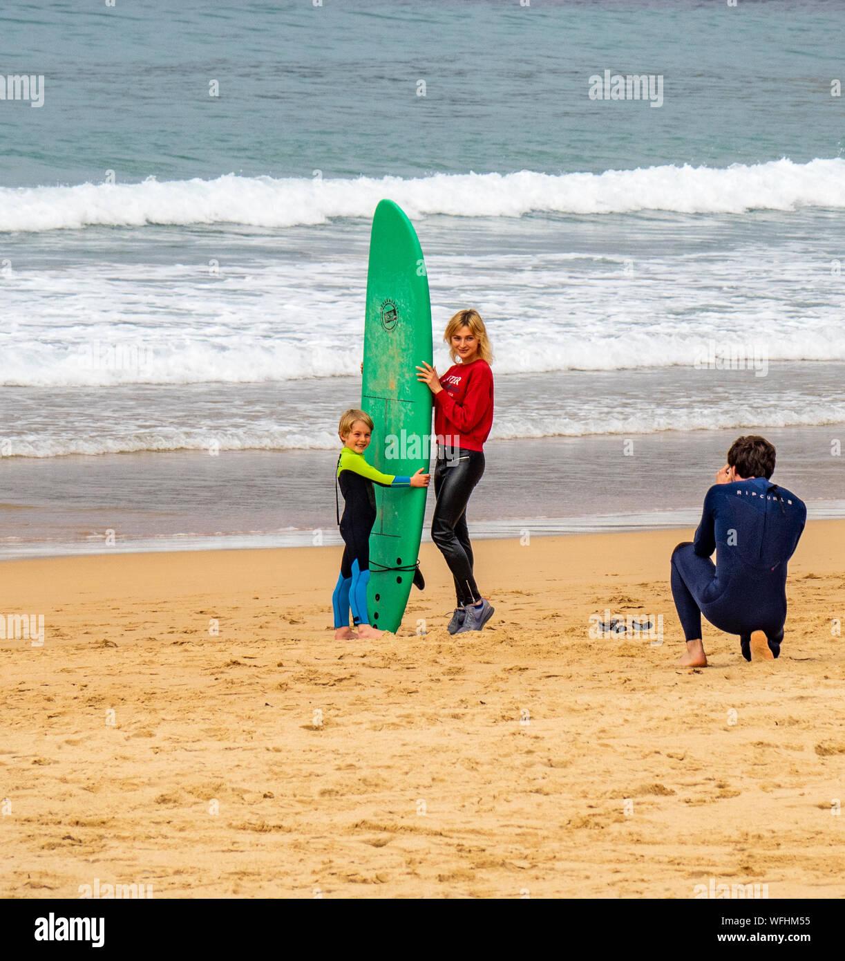 Padre di prendere una fotografia di madre e figlio tenendo un green con la tavola da surf a Manly Beach Sydney NSW Australia. Foto Stock