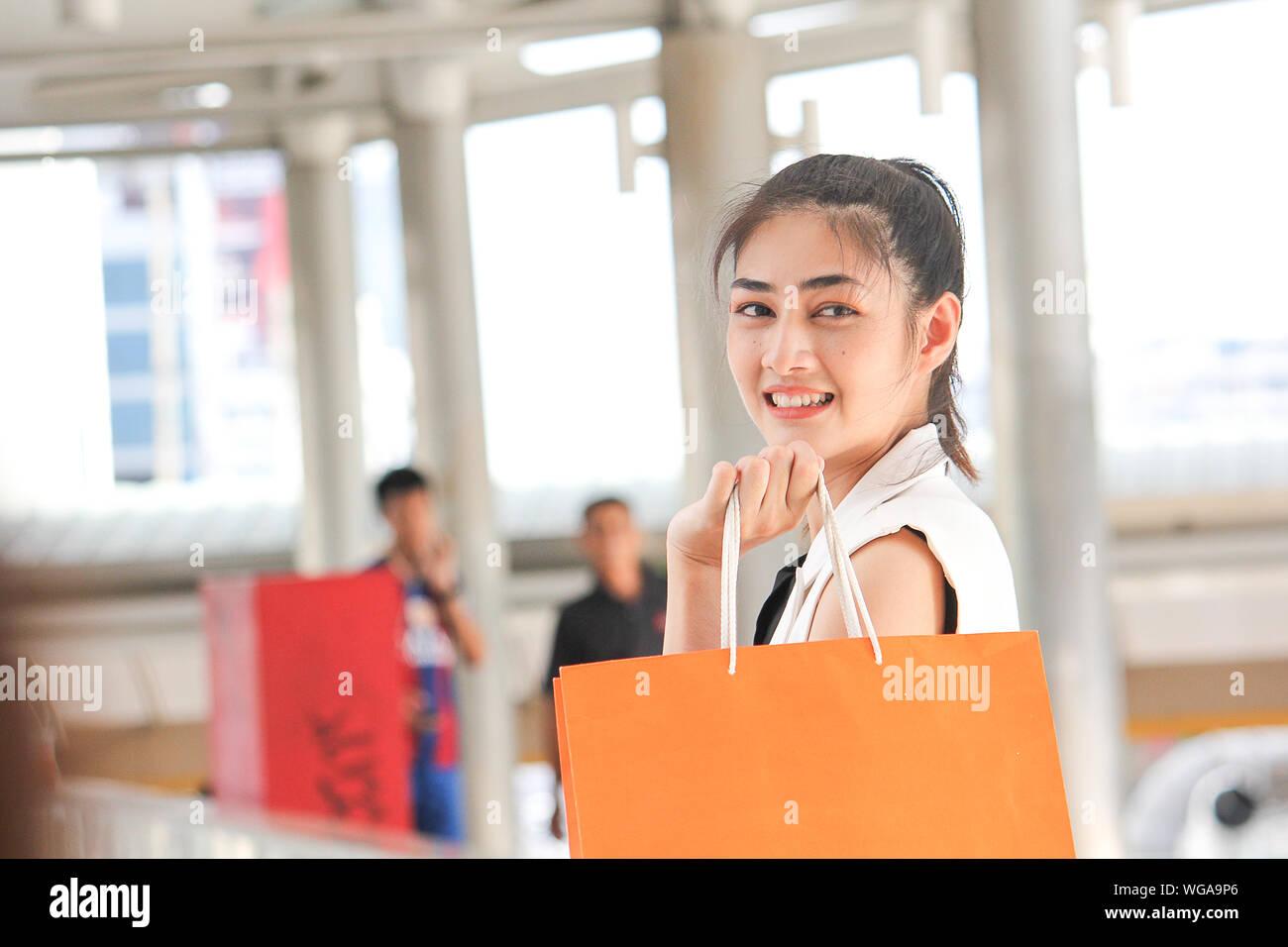 Vista laterale Ritratto di sorridente giovane donna azienda borse per lo Shopping nel ponte di coperta Foto Stock