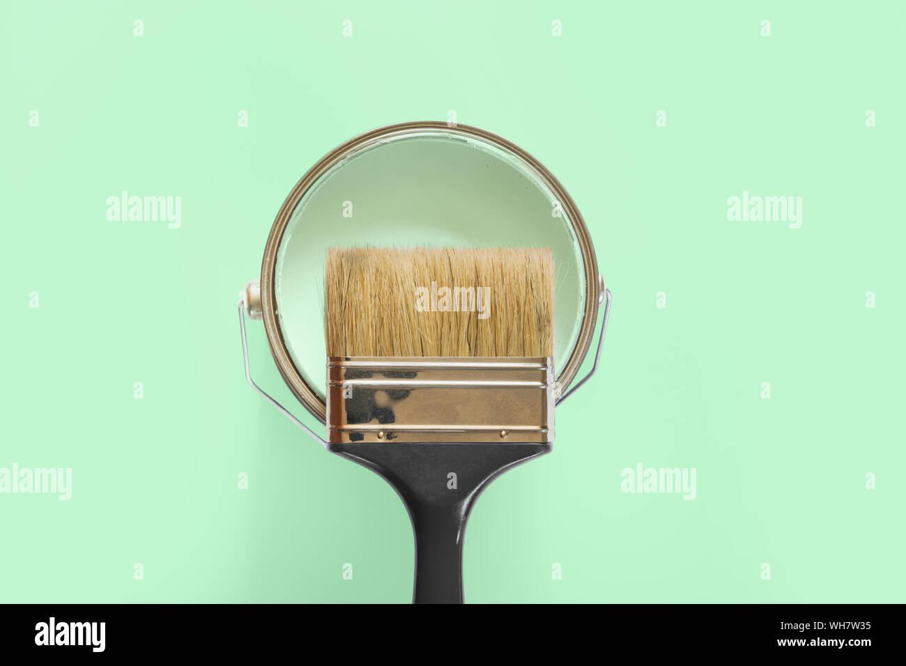 Nero con spazzola aperto può di menta di vernice sul neo Sfondo menta. Le riparazioni di tendenza concetto. Foto Stock