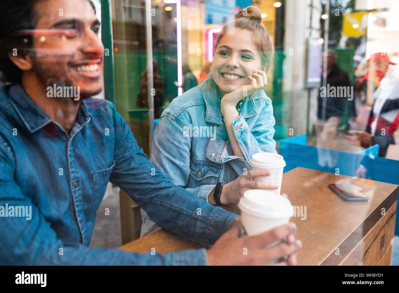 Ritratto di sorridente giovane donna in una caffetteria guardando il giovane uomo Foto Stock